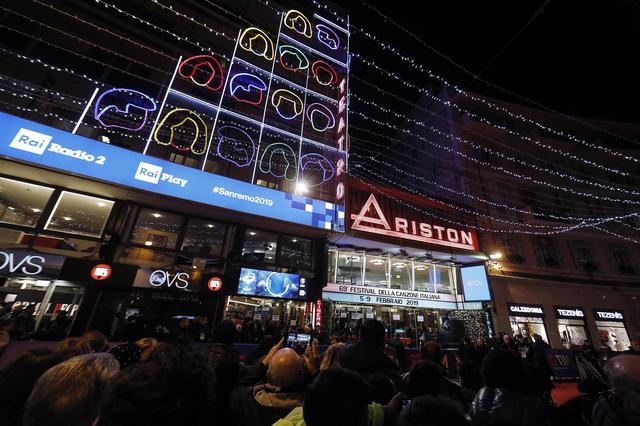 A foto mostra a frente do Tetaro Ariston, sede dos festivais Sanremo, com a fachada luminosa e muitas pessoas indo até a porta.