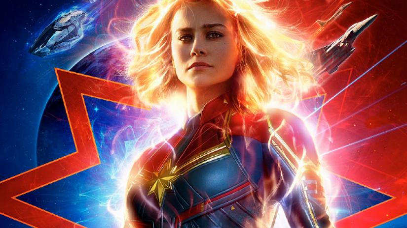 A imagem mostra a Capitã Marvel com seu uniforme vermelho, azul e amarelo e seu corpo emanando uma luminosidade amarela e poderosa que se assemelha aos raios solares