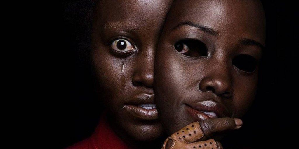 A foto mostra a personagem principal com um olhar transtornado e lacrimejando, enquanto segura em frente ao seu rosto uma mascara idêntica a sua face, porém com uma expressão alegre