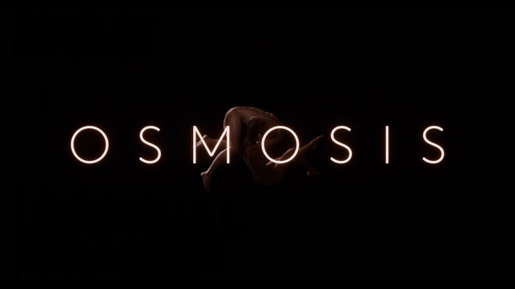 Duas pessoas brancas e nuas se entrelaçando atrás do letreiro luminoso do nome da série e um fundo escuro.